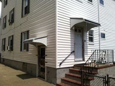 Two aluminum awnings on the back entrances on a multi-family home in New Bedford.