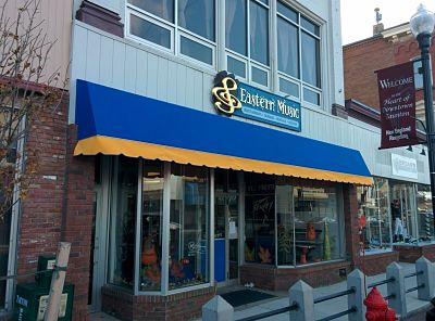 A two tone awning in Taunton, MA adds a colorful pop to this local music shop's storefront.