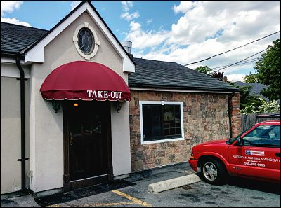 A half round entrance awning with painted on lettering  that fits in with with the old fashioned look of this restaurant.