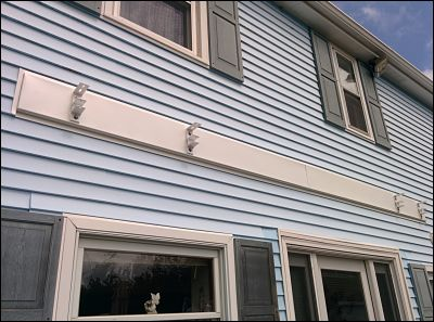 An aluminum covered beam neatly tucked into this house's vinyl siding.