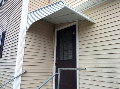 This aluminum awning sits side saddle over this door, as there was not enough head room or a level mounting surface to put it up traditionally.