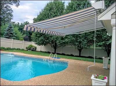A side view of this retractable awning, partially covering the deep end of the pool.