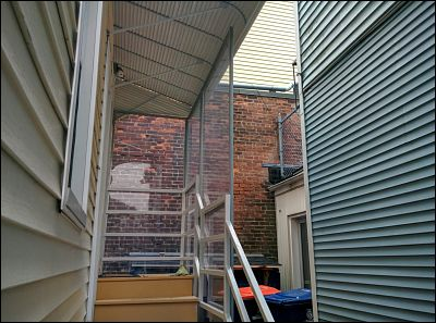 An underneath view of an aluminum awning with a glass wall, separating this tenant from their neighbor.