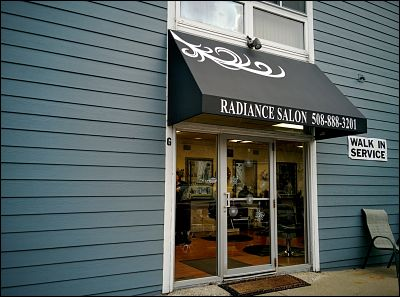 An entrance awning with graphics for a local hair salon.
