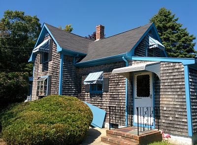 This house in Fairhaven, MA will reap the benefits of both and aluminum door canopy as well as canvas window awnings.